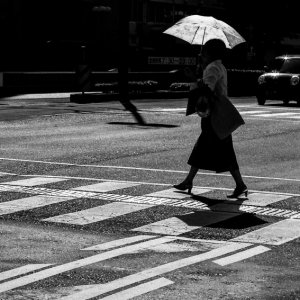 Woman with sunshade crossing