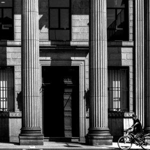 コリント様式の柱の前を走る自転車