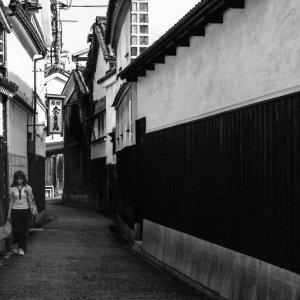 薄暗い路地を歩く若い女