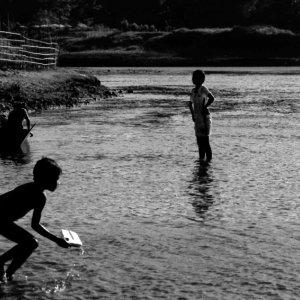 川の中で遊ぶシルエットになった子どもたち