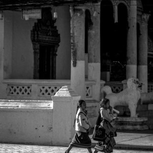 Two girls walking in front of Buddhist temple