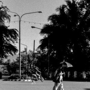 Buddhist monk crossing street with sunshade