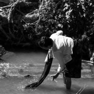 小川の中で洗濯をする女