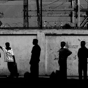 Silhouettes of people waiting at bus stop