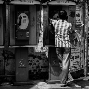 Man calling from telephone booth