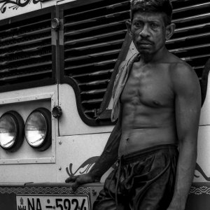 Driver standing in front of bus