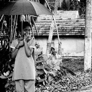 雨の中で傘を片手にウインクする女の子