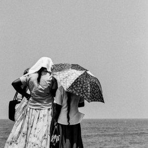 Women watching fishermen working on beach