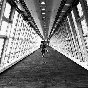 Man walking glass-made corridor