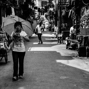 日傘を手に路地を歩く女性