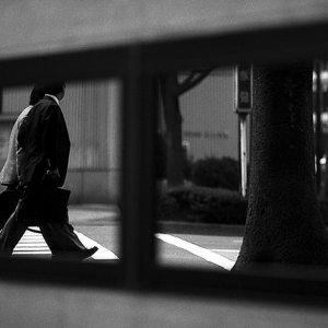 Two businessmen walking in front of mirror