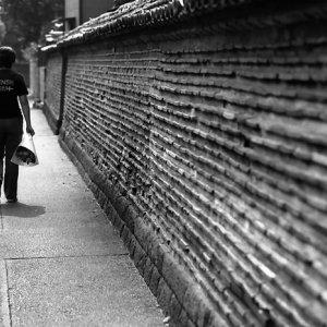People walking along wall