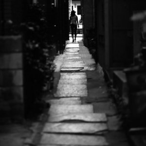 figure in stone-paved lane