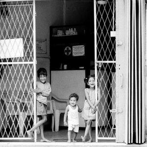 門のところに立つ三人の子ども