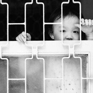 Boy looking through window lattice