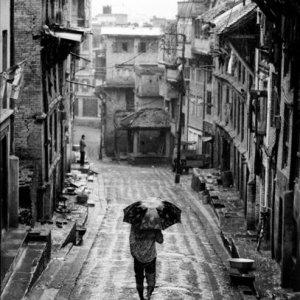 傘を差して坂道を下る男