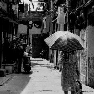 日傘を差して路地を歩く女性
