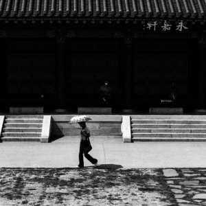 Woman with umbrella walking in front of hall