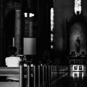 薄暗いマニラ大聖堂で参拝する信者