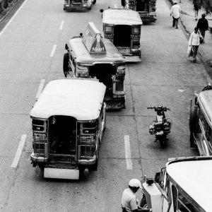 Policeman standing beside jeepney