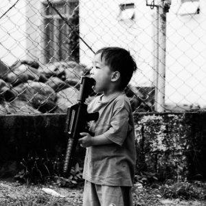 銃を咥えた男の子