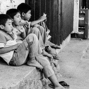 道端に並んで腰掛けた三人の男の子