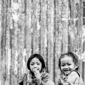 トタン板の壁の前に腰掛けるふたりの女の子