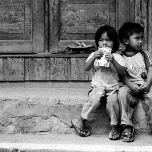 Boy and girl sitting close by the wayside