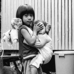 抱えた赤ん坊の目を隠す女の子
