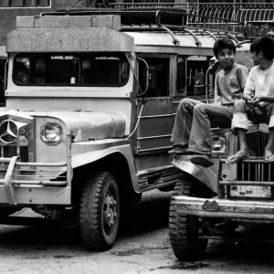 Two boys sitting on the hood of a jeepney