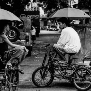 Pedicab drivers chatting under umbrella