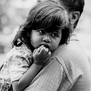 Little girl being held in father's arms