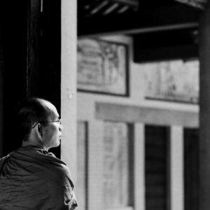 扉のところに佇む袈裟を纏った僧侶