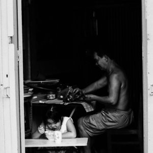 Girl eating and father working