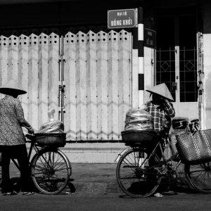 Women wearing conical hat standing by roadside