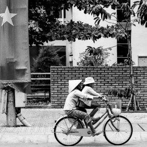 ベトナム国旗の前を通り過ぎる自転車