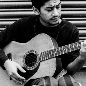 寺院の境内でギターを弾く男