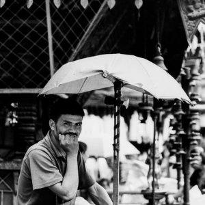 Rickshaw wallah waiting for customer under umbrella