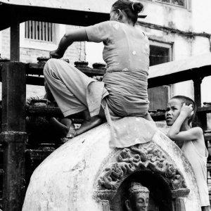仏像の上に腰を下ろして掃除する女
