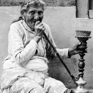軒下で水煙草を吸う老婆