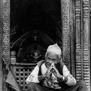 Old man sitting in front of small shrine