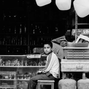 Boy sitting in storefront