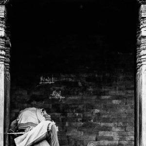 木の柱の間で昼寝する男
