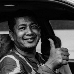 親指を立てるタクシーの運転手