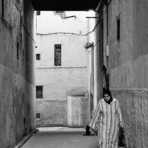 路地を歩くジュラバを着た女