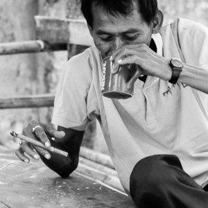 Man smoking a cigar and drinking coffee