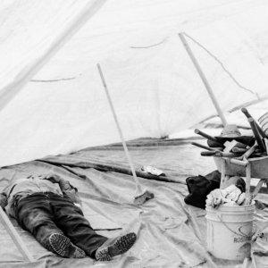 テントの中で寝る男