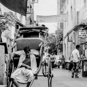 Rickshaw wallah looking lifeless on his vehicle