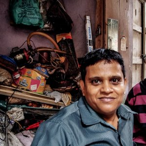 Two men in front of junkyard