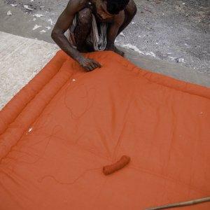 赤いクッションを縫う男